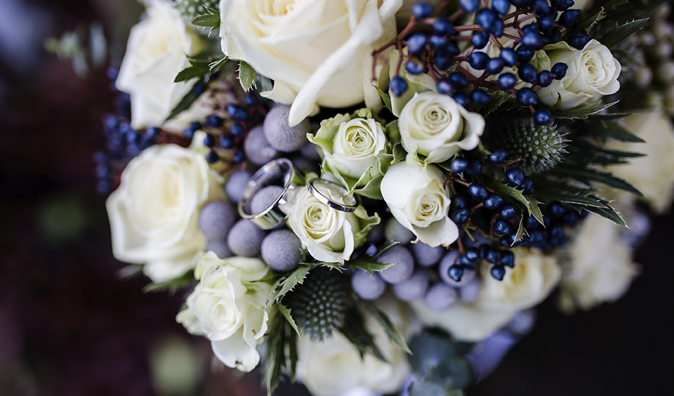 Mixed purple blooms and berries with pale roses and seasonal foliage for the perfect winter wedding bouquet for your wedding at Clock Barn