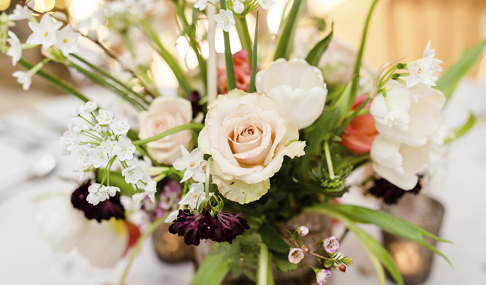 Arrangements of pale roses and delicate deep pink flowers with lush green foliage are perfect for decorating your tables at your barn wedding in Hampshire