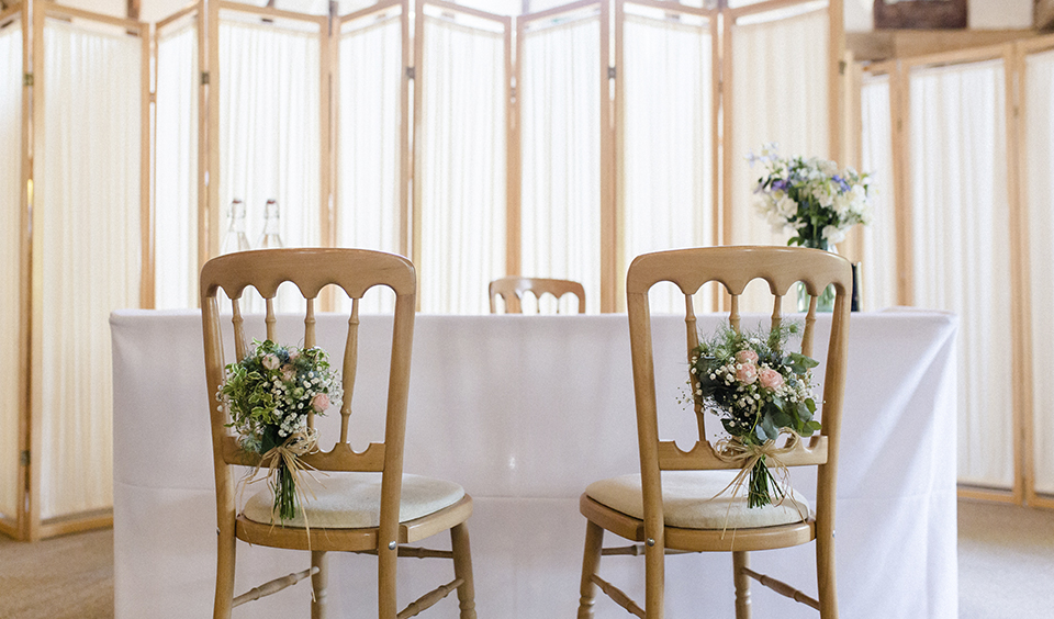 Decorate the chairs for your summer wedding ceremony with delicate pink flowers and lots of lush foliage at Clock Barn in Hampshire