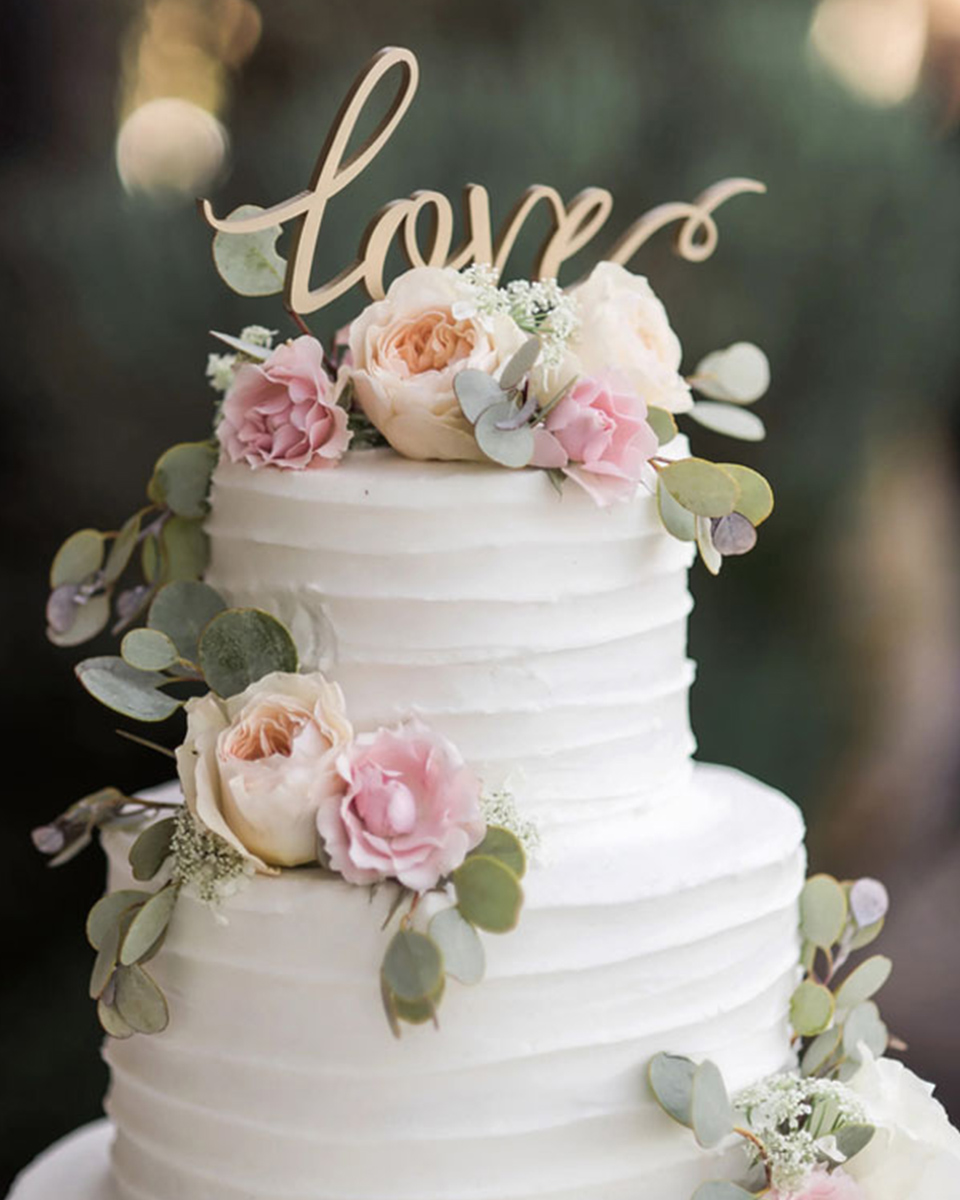 A romantic wedding message on a cake topper adds the perfect touch to your pretty wedding cake at your rustic barn wedding in Hampshire