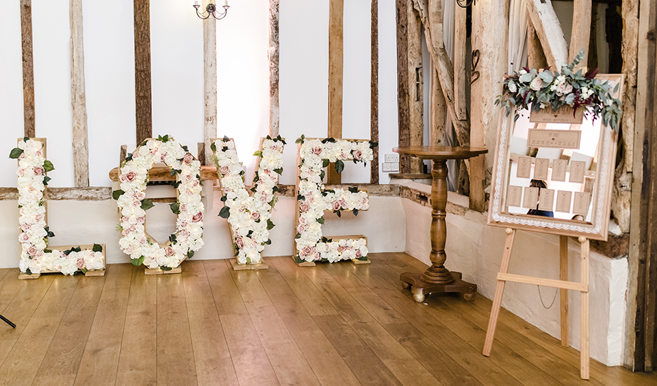 Floral love letters looked perfect in the rustic barn at this wedding at Clock Barn in Hampshire
