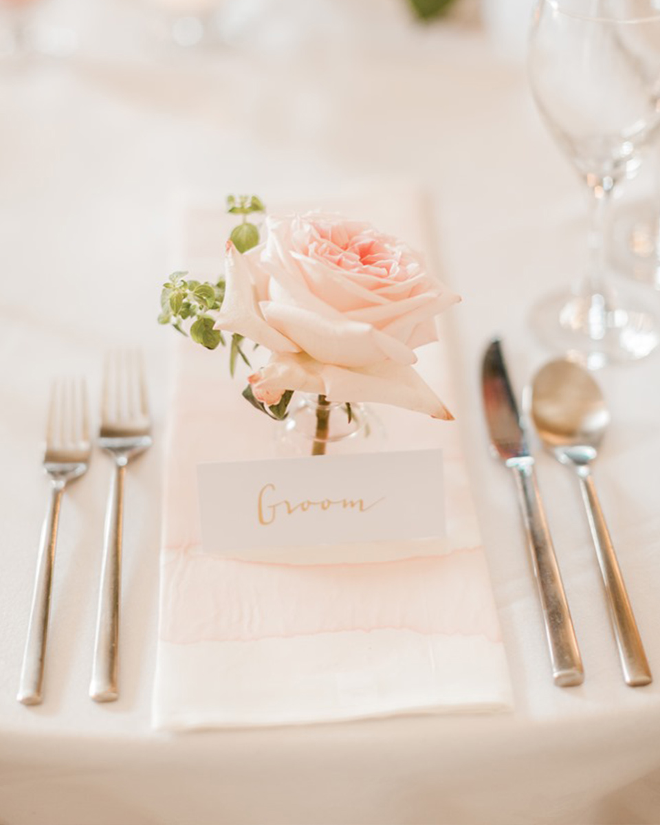 A freshly cut soft pink rose at each place setting adds a touch of romance to your wedding décor at Clock Barn in Hampshire