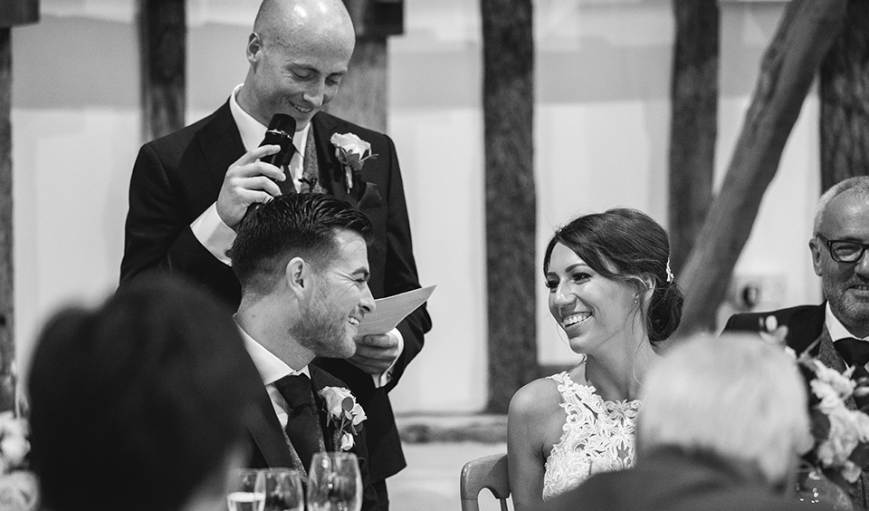 The bride and groom enjoyed the best man's speech at their rustic barn wedding in Hampshire