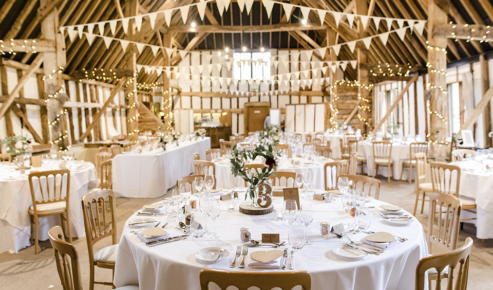 The rustic barn looked beautiful with a touch of decoration and pretty floral arrangements on the tables at Clock Barn in Hampshire