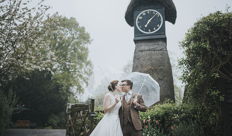 The happy couple pose for a wedding photo in front of the clock tower at Clock Barn in Hampshire