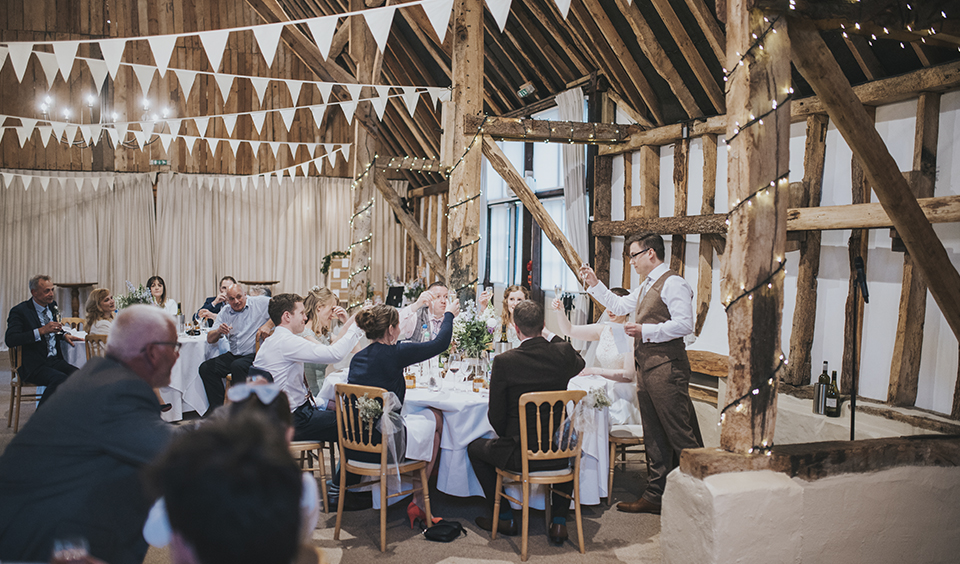 The guests raise a glass as the groom makes his speech at this rustic barn wedding in Hampshire