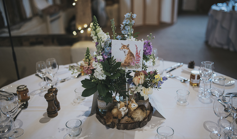 Displays of pretty spring flowers and rustic wedding decorations were used as table centrepieces at this rustic barn wedding
