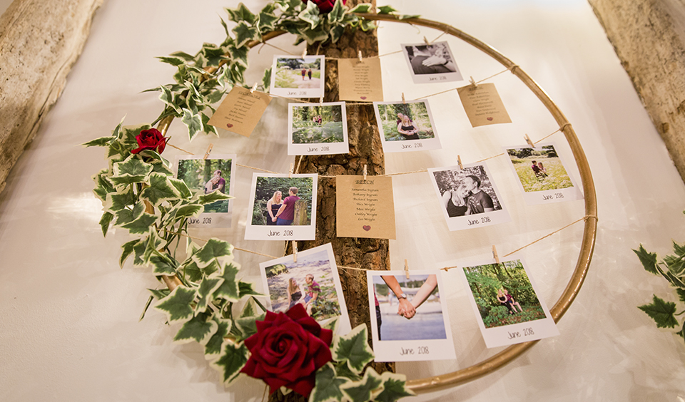The seating plan was displayed on a wooden hoop decorated with ivy and red roses at this rustic barn wedding in Hampshire