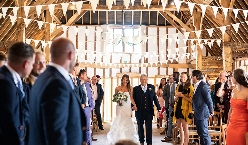 The bride walks down the aisle with her father at this wedding ceremony at Clock Barn in Hampshire