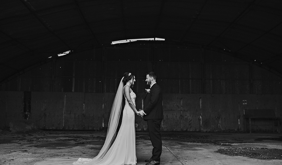 The happy newlyweds have their wedding photos taken in the disused barn at Clock Barn in Hampshire