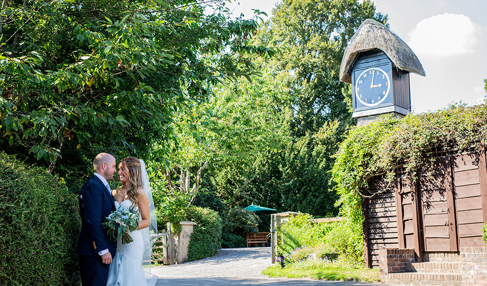 The happy newlyweds pose for a wedding photo in front of the Clock Tower at Clock Barn