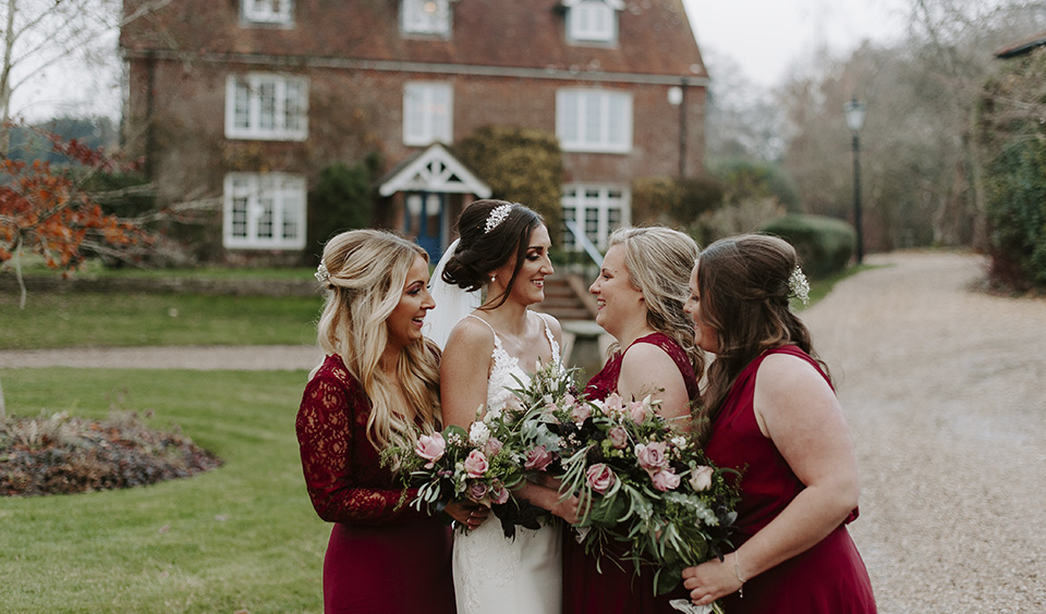 The bridesmaids wore deep red bridesmaid dresses in different styles at this barn wedding in Hampshire