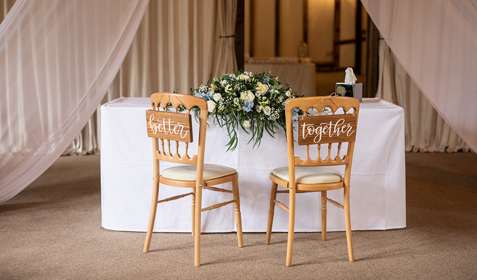 The couple chose wooden wedding signs for the back of their wedding ceremony chairs at Clock Barn in Hampshire