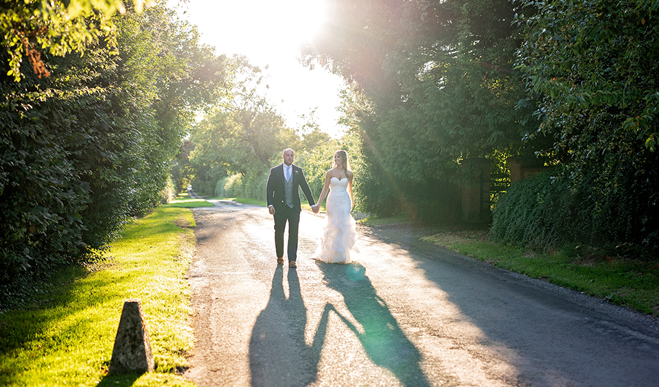 The happy couple take a moment away from the celebrations to enjoy a stroll in the sunshine at their Clock Barn wedding