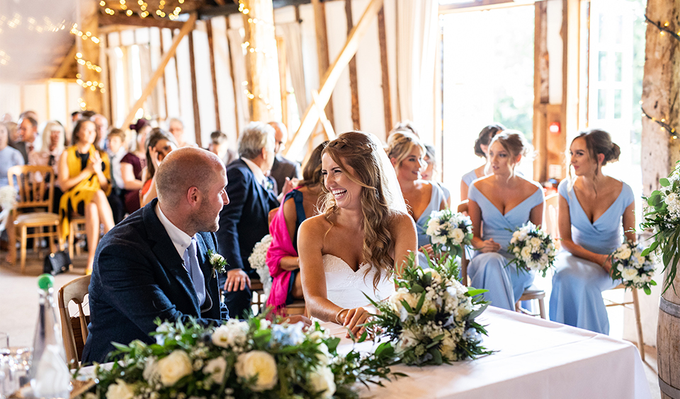 The happy newlyweds get ready to sign the register following their wedding ceremony at Clock Barn