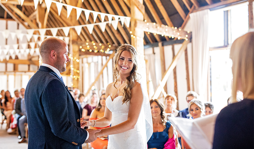 The happy couple say their vows at their wedding ceremony at Clock Barn in Hampshire