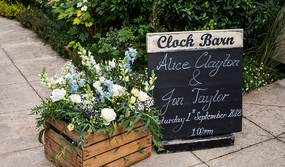 Pretty summer wedding flowers were displayed in a crate at this barn wedding in Hampshire