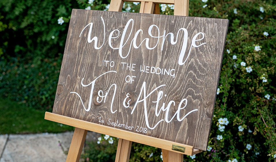 A wooden wedding sign welcomed guests to this wedding at Clock Barn in Hampshire