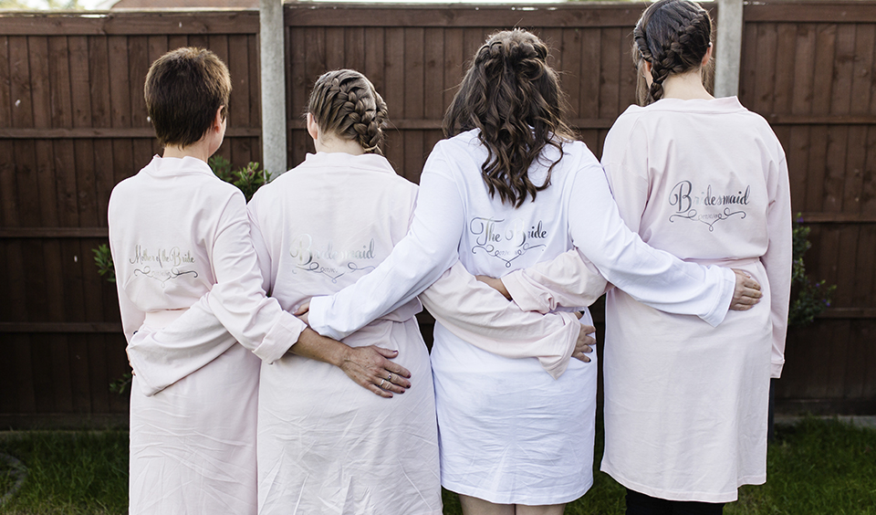 The bride and bridesmaids wear matching dressing gowns as they prepare for the day ahead