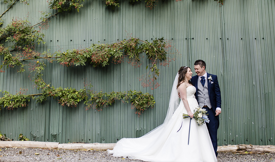 The bride and groom have wedding photos taken by the old cow shed at Clock Barn in Hampshire