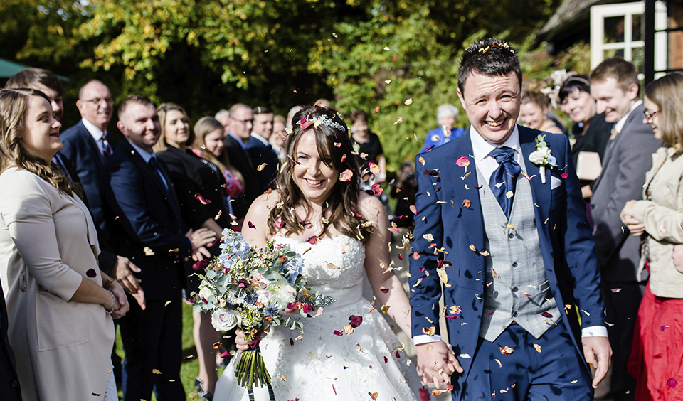 The happy newlyweds have confetti thrown over them following their wedding ceremony at Clock Barn in Hampshire