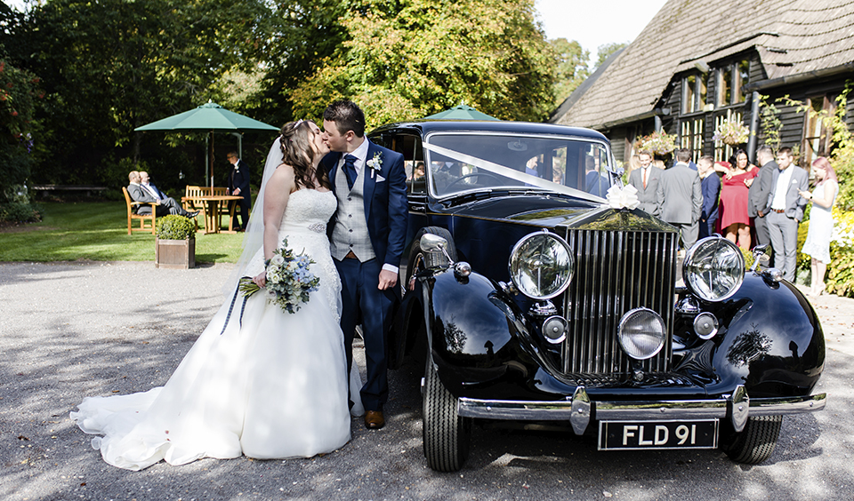 The bride and groom share a wedding kiss as they stand by the wedding car at Clock Barn